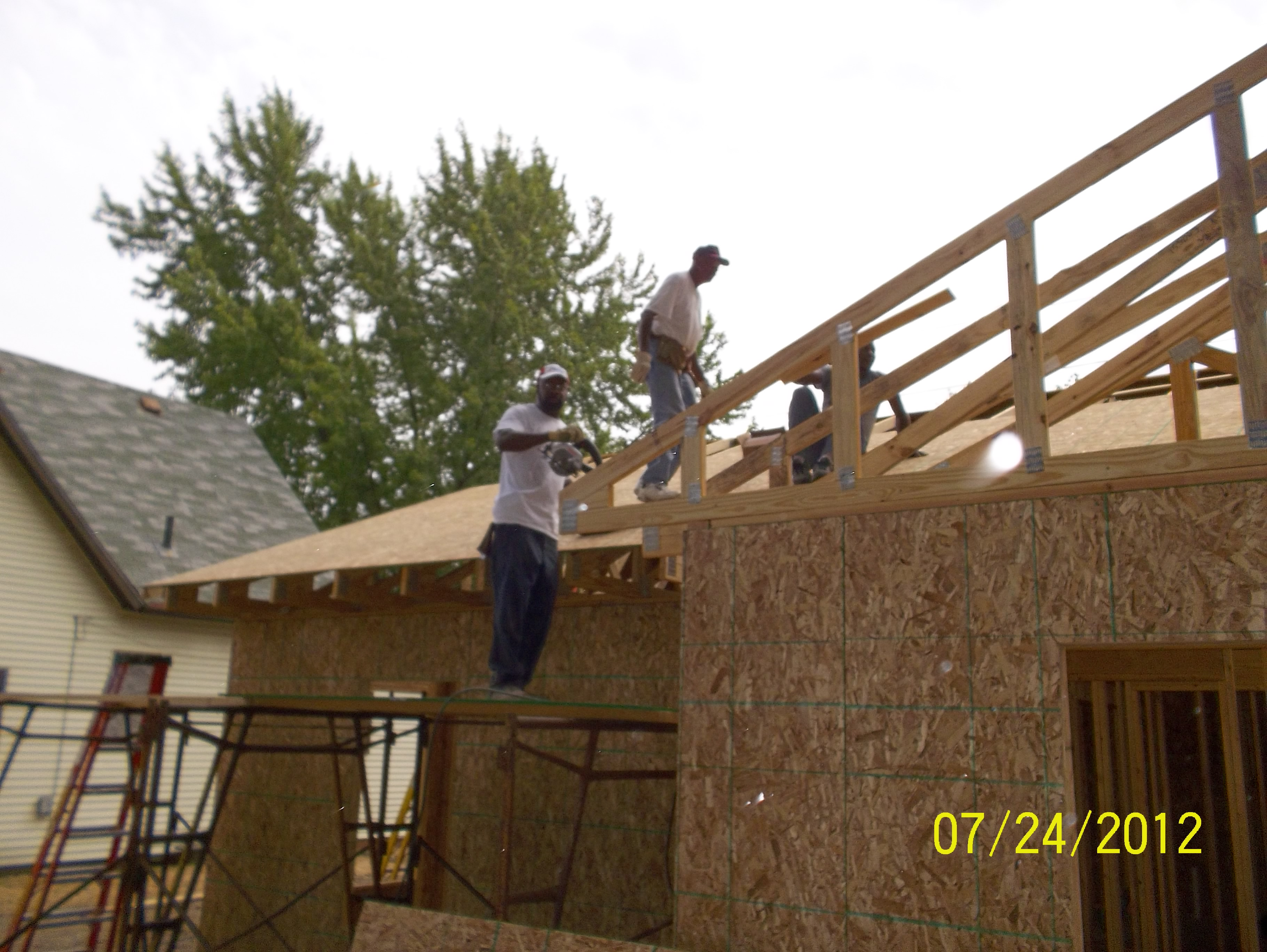 Trusses are in and volunteers apply roof decking