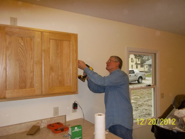 Mike and Rand Campbell, past HFHD president, install kitchen cabinets
